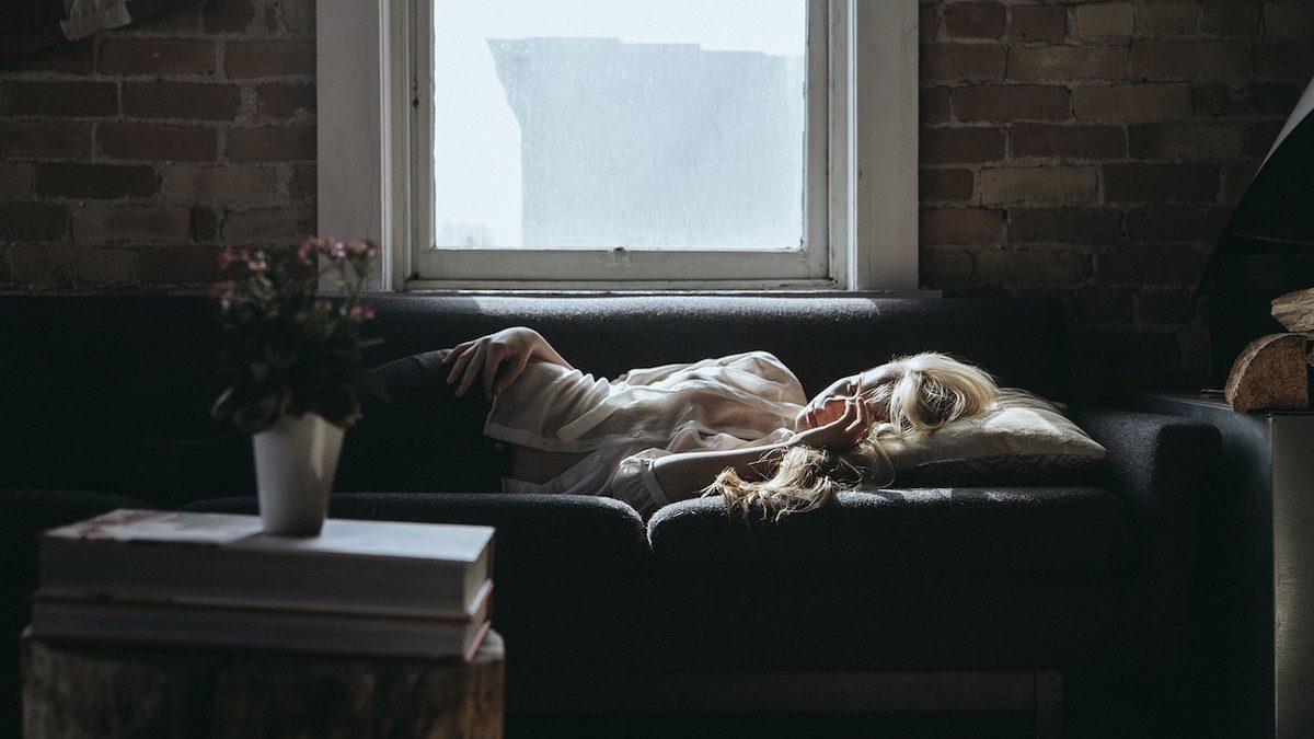 Jeune femme épuisée, dormant dans son canapé